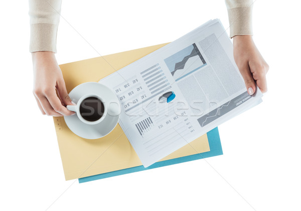 Stock photo: Business woman having a coffee at office desk