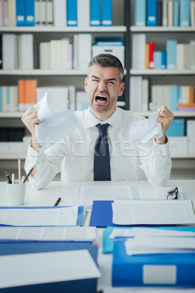Angry businessman working at office desk Stock photo © stokkete