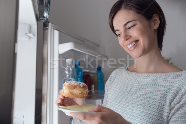 Woman taking a pastry out of the fridge Stock photo © stokkete