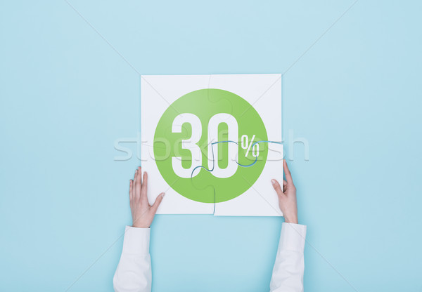 Woman completing a puzzle with a 30% off discount icon Stock photo © stokkete