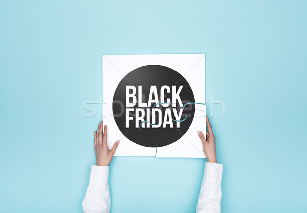 Woman completing a puzzle with a black friday badge Stock photo © stokkete
