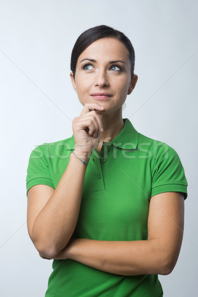 Smiling woman thinking with hand on chin Stock photo © stokkete