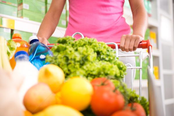 Foto stock: Completo · carrinho · de · compras · mulher · supermercado · empurrando · frutas · frescas