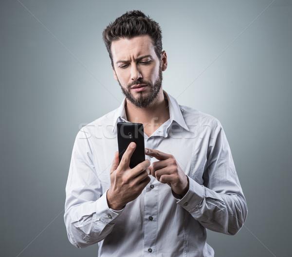 Deluso uomo digitando smartphone giovane touch screen Foto d'archivio © stokkete