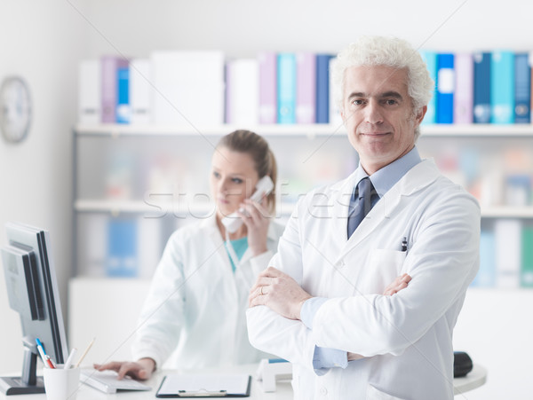A doctor with his assistant in the office Stock photo © stokkete