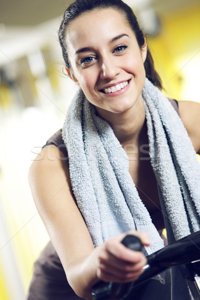 A young woman riding an exercise bike Stock photo © stokkete