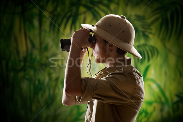 Young explorer looking through binoculars Stock photo © stokkete