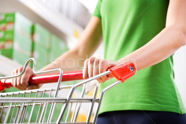 Stockfoto: Vrouw · supermarkt · groene · tshirt · voortvarend · winkelwagen