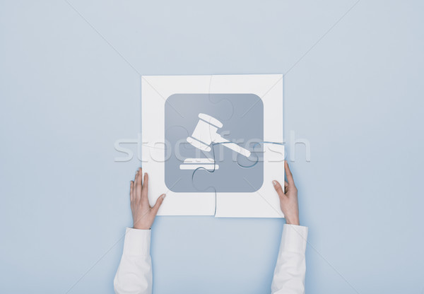 Woman completing a puzzle with a gavel icon Stock photo © stokkete