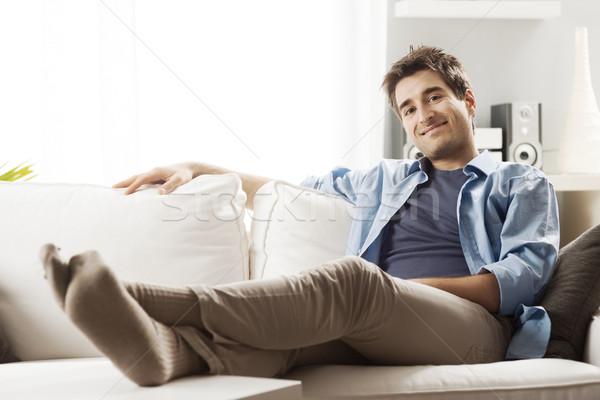 Fiatalember megnyugtató kanapé nappali mosolyog kamera Stock fotó © stokkete