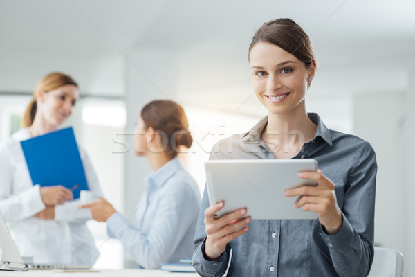 Smiling business woman using a tablet Stock photo © stokkete
