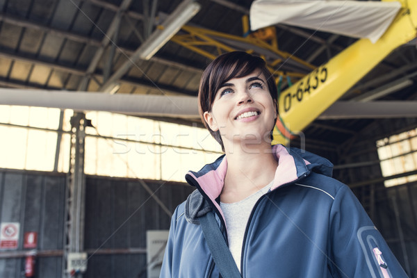 Smiling young pilot posing with a propeller plane Stock photo © stokkete