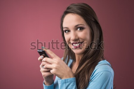 Smiling teenager with smartphone Stock photo © stokkete