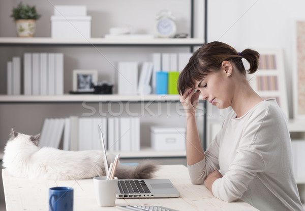Woman with headache sitting at desk Stock photo © stokkete