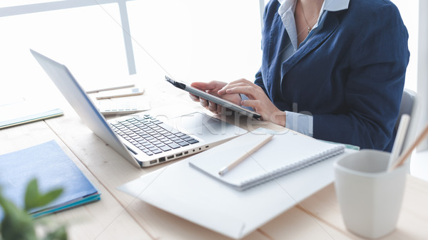 Stock photo: Businesswoman using a touch screen tablet