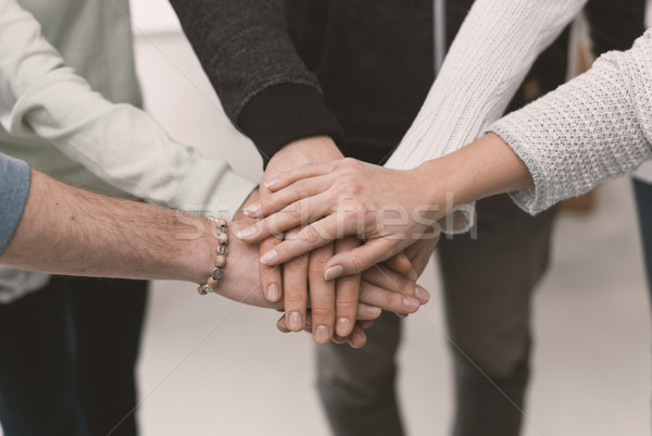 Young people stacking hands Stock photo © stokkete