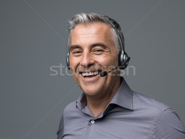 Smiling customer support phone operator Stock photo © stokkete