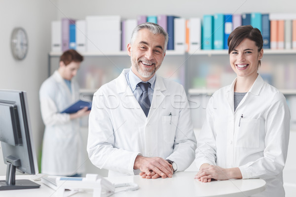 врач при столе помощник улыбаясь камеры Сток-фото © stokkete