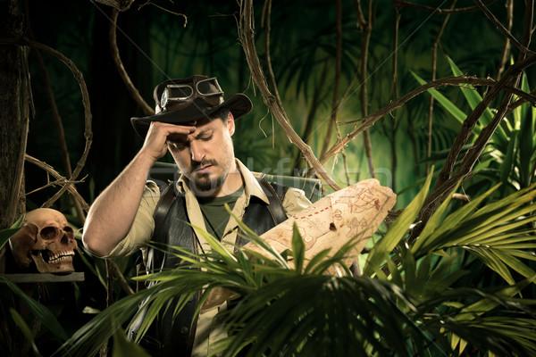 Stock photo: Lost explorer examining a map