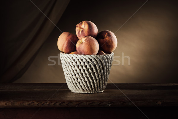 Ripe peaches in a basket still life Stock photo © stokkete