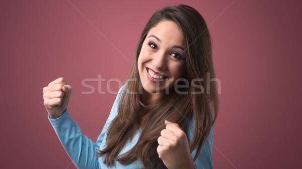 Joyful woman with raised fists Stock photo © stokkete