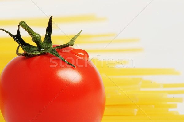 Tomato with drops and uncooked spaghetti noodleson background Stock photo © stokkete