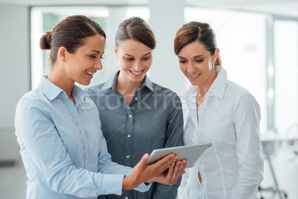 Female business team using a digital tablet Stock photo © stokkete