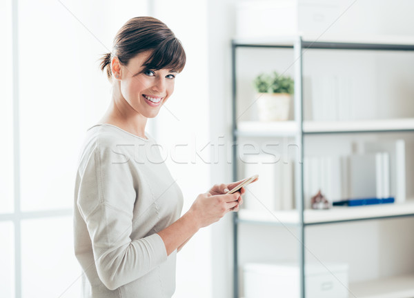 Stock photo: Confident woman using a smart phone