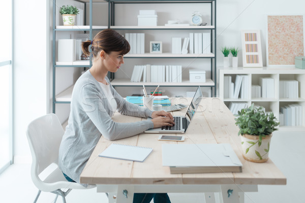 Confident businesswoman working at desk Stock photo © stokkete