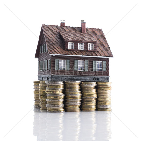 Model house with piles of coins as foundation Stock photo © stokkete