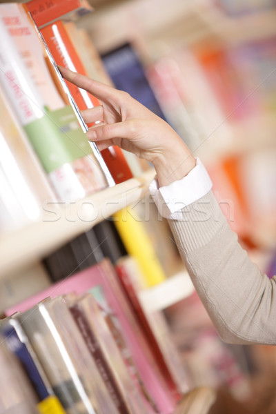young woman looking for a book in a bookstore - hand close up Stock photo © stokkete