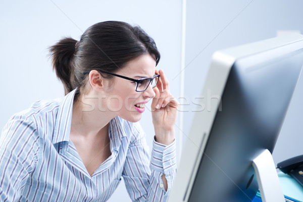 Office worker staring at computer screen Stock photo © stokkete