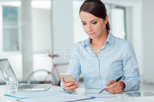 Stock photo: Confident business woman using a smart phone