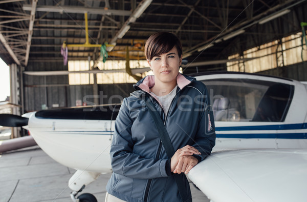 Female pilot posing in the hangar Stock photo © stokkete