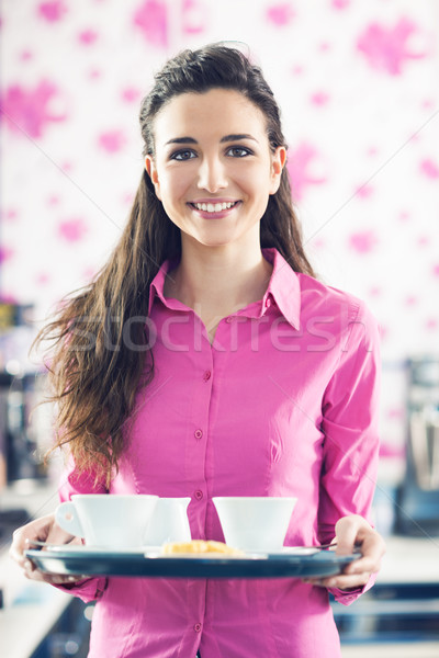 Young smiling waitress serving coffee at the bar Stock photo © stokkete