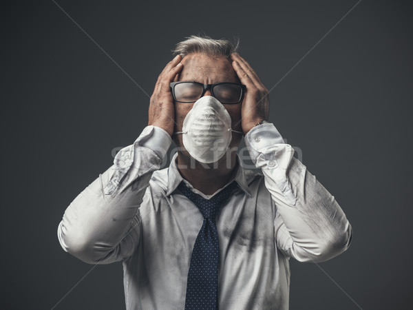 Businessman with mask and head in hands Stock photo © stokkete