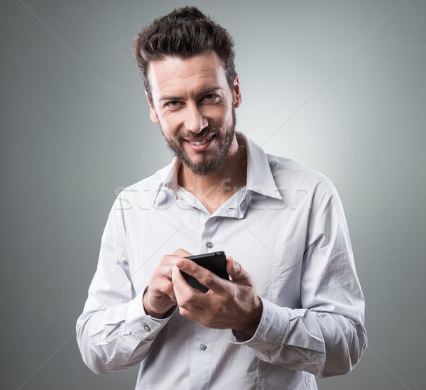 Mosolyog üzletember okostelefon mobil érintőképernyő telefon Stock fotó © stokkete