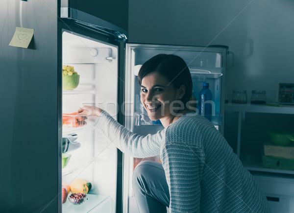Woman taking food out of the fridge Stock photo © stokkete