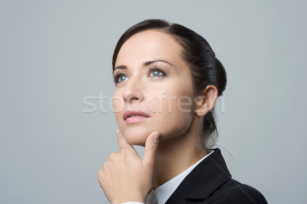 Pensive businesswoman with hand on chin Stock photo © stokkete