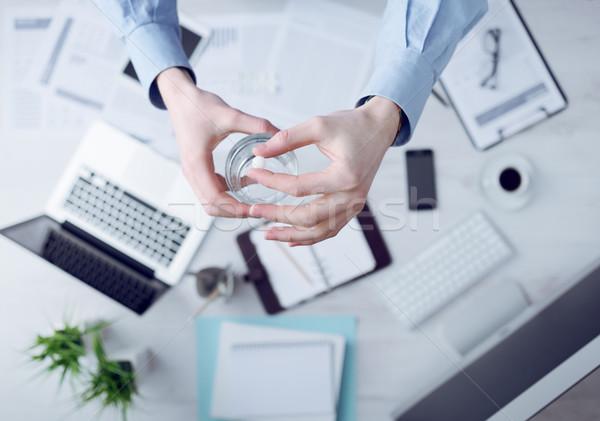 Office worker taking a pill Stock photo © stokkete