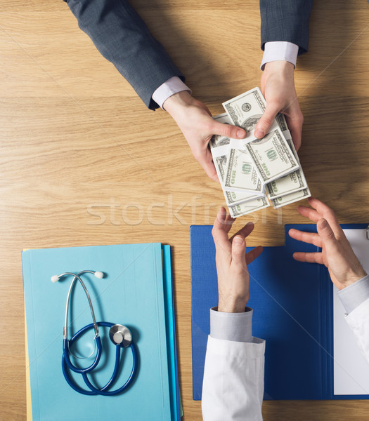 Patient bribing a greedy doctor Stock photo © stokkete
