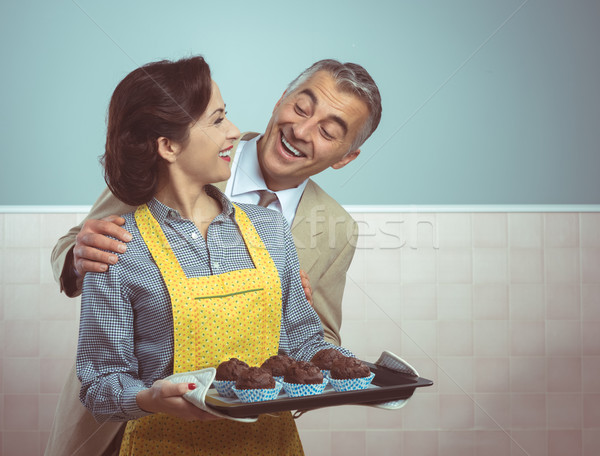 Vintage woman cooking muffins for her husband Stock photo © stokkete