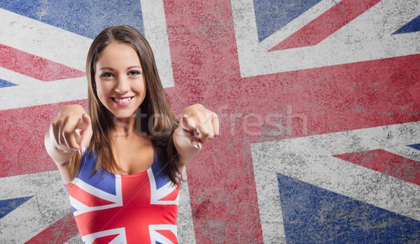 Mosolyog lány mutat kamera visel brit zászló Stock fotó © stokkete