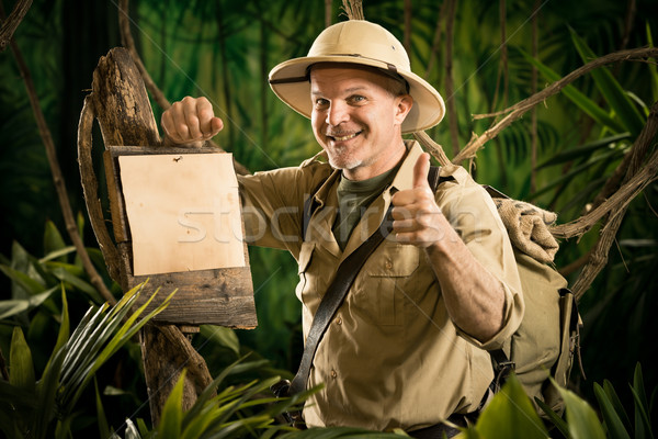 Cheerful explorer thumbs up with sign Stock photo © stokkete