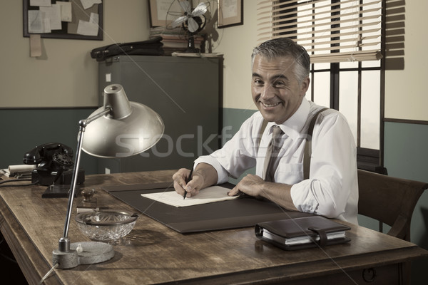 Director at desk signing a document Stock photo © stokkete
