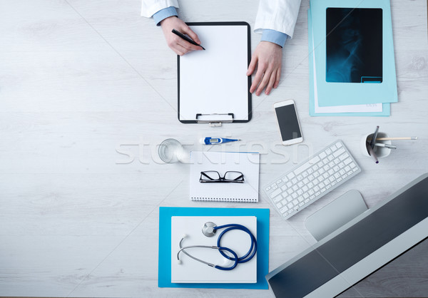 Doctor writing medical records Stock photo © stokkete