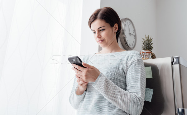 Woman texting in the kitchen Stock photo © stokkete