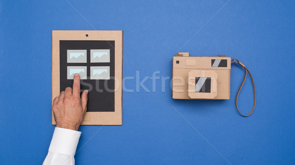 Viewing pictures on a carboard tablet Stock photo © stokkete