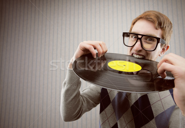 Nerd student angry, biting a vinyl record Stock photo © stokkete