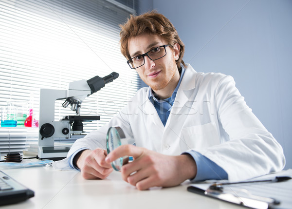 Chemical laboratory technician holding magnifier Stock photo © stokkete